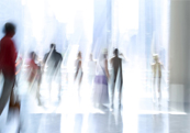 A high contrast blurred picture of several people moving through a plaza to represent Talascend's community of engineering and technical industry contractors, candidates and talent network